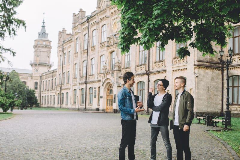 Pomyślni szczęśliwi ucznie stoi blisko kampusu lub uniwersyteta outside obrazy royalty free