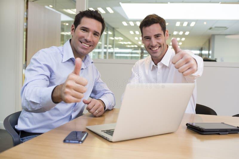 Pomyślni uśmiechnięci biznesmeni w biurze, przyglądająca kamera, daje fotografia royalty free