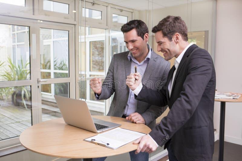 Pomyślni uśmiechnięci biznesmeni w biurze, z rękami up obrazy stock