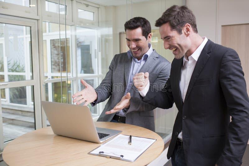 Pomyślni uśmiechnięci biznesmeni w biurze, z rękami up fotografia royalty free