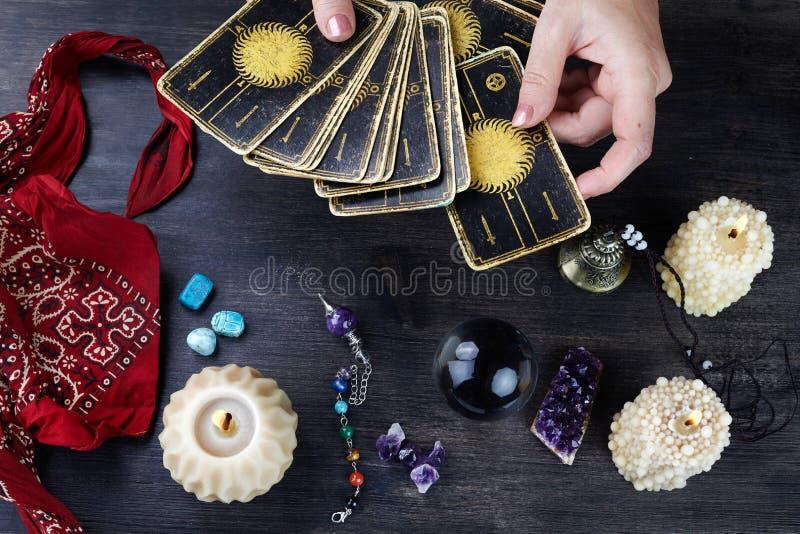 Pomyślność narratora kobiety ręki i tarot karty na ciemnym drewnianym stole Wr??by poj?cie zdjęcie stock