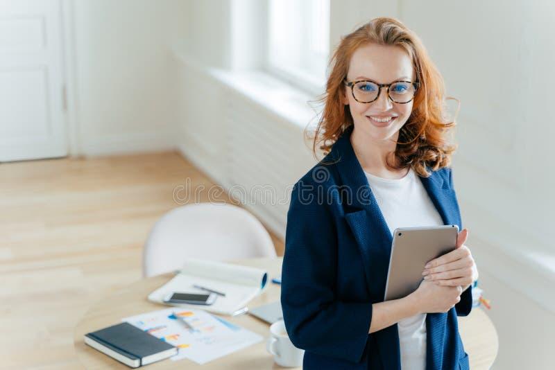 Pomyślny żeński lider pracować drużyny trzyma cyfrowego pastylka przyrząd, rozwija biznesowych pomysły, toothy uśmiech, czerwony  zdjęcie royalty free