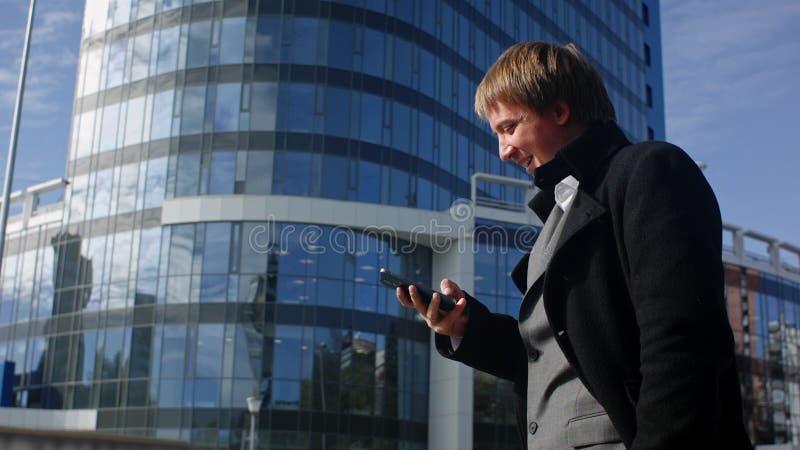 Pomyślny biznesmen czyta wiadomość na jego smartphone zdjęcia royalty free