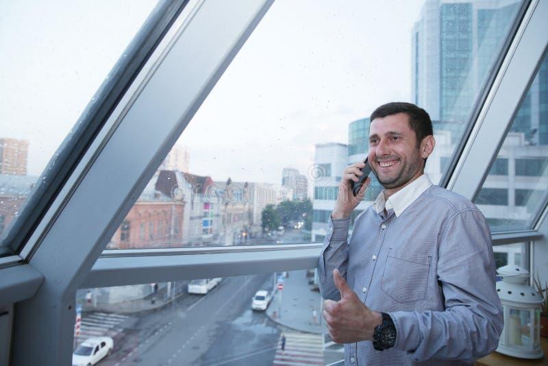 Pomyślny biznesmen opowiada na telefonie komórkowym z uśmiechem na jego twarzy trzyma jego kciuk w górę tła panoramiczny przeciw obraz royalty free
