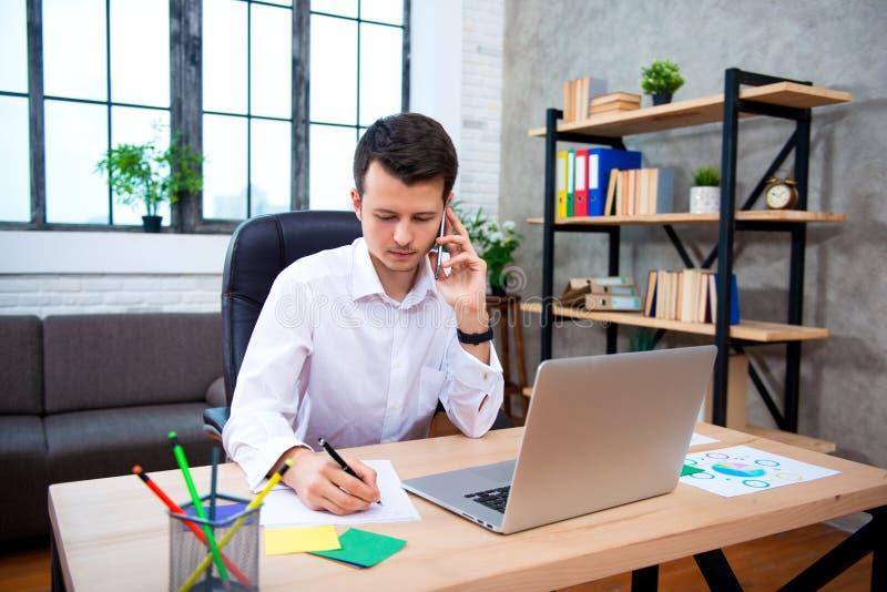 Pomyślny biznesmen opowiada na telefonie używać laptopu obsiadanie, młodego przedsiębiorcy mężczyzny mówienie przy biurem, komórk obraz royalty free