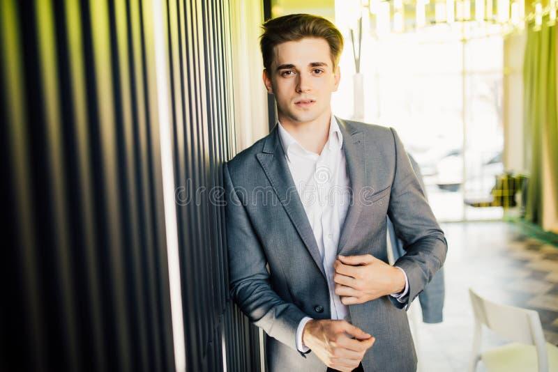 Pomyślny biznesmen ubierający w drogim kostiumu stoi w korytarzu jego firmy Młody męski kierownik pozuje w nowożytnym biurze fotografia royalty free