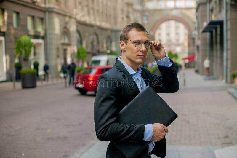 Pomyślny biznesmen w kostiumu z laptopem w mieście obrazy royalty free
