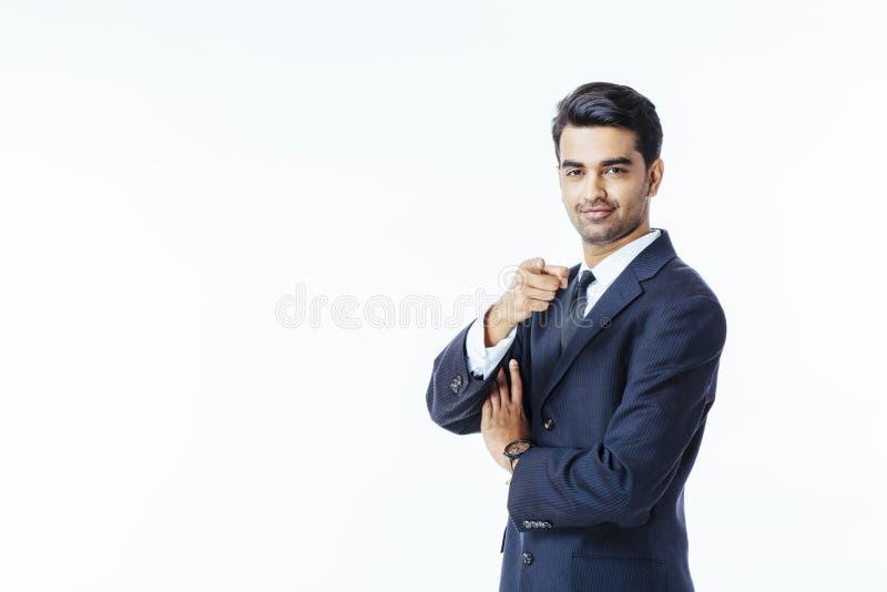 Pomyślny biznesmen wskazuje przy kamerą w czarnym krawacie i kostiumu obraz royalty free
