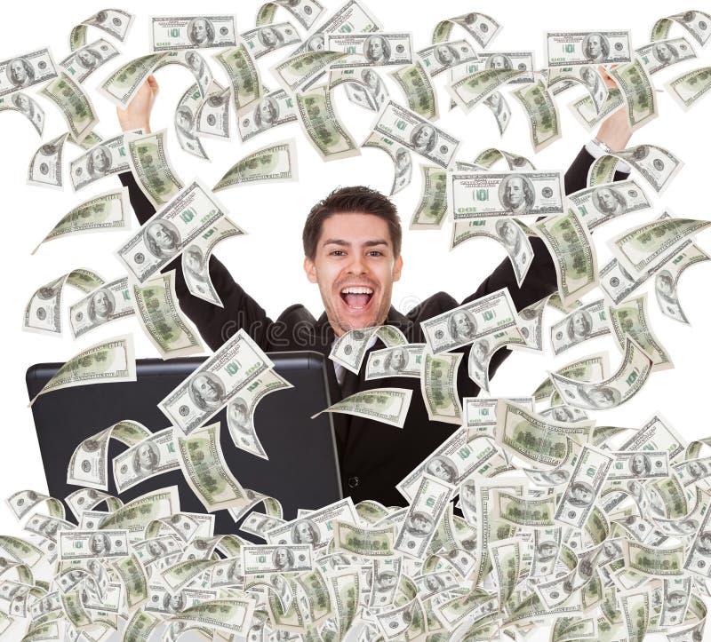 Pomyślny biznesmen z pieniądze deszczem zdjęcia stock
