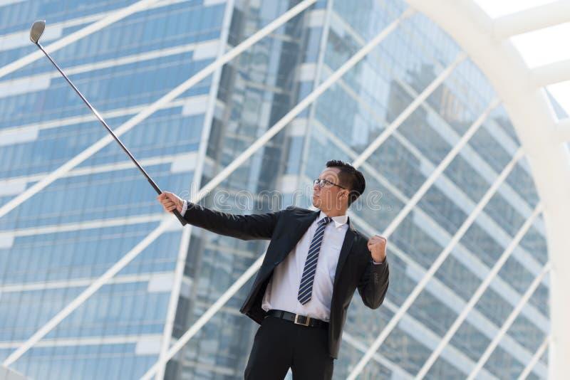 pomyślny biznesmena kostium ręka trzyma golfowego wyposażenie stan zdjęcie stock