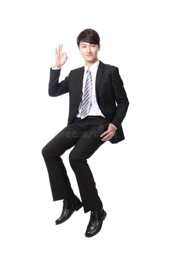 Pomyślny biznesowego mężczyzna obsiadanie na coś obrazy royalty free