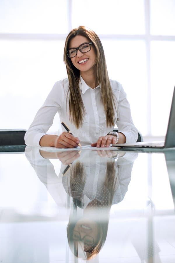 Pomyślny biznesowej kobiety obsiadanie przy biurowym biurkiem fotografia royalty free