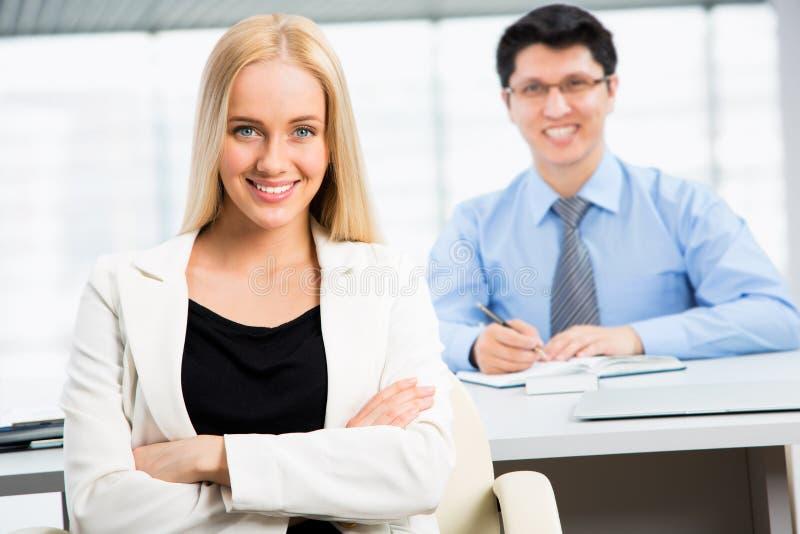 Pomyślny biznesowej kobiety obsiadanie z jej kolegą przy biurem obraz stock