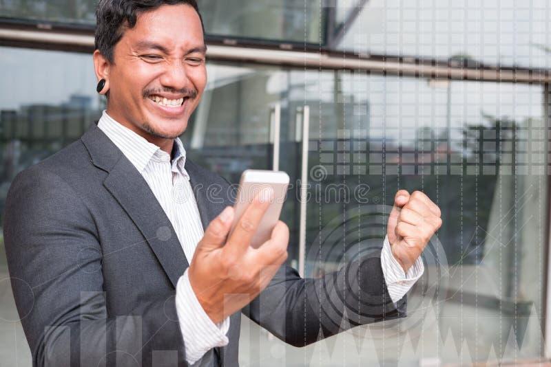 Pomyślny biznesowy mężczyzna sprawdza telefonu komórkowego gestykulować i wiadomość obrazy royalty free