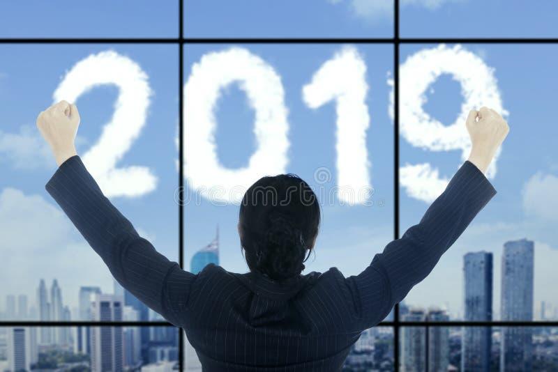 Pomyślny bizneswoman patrzeje liczby 2019 obraz stock
