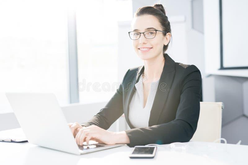 Pomyślny bizneswoman Pozuje przy biurkiem obraz stock