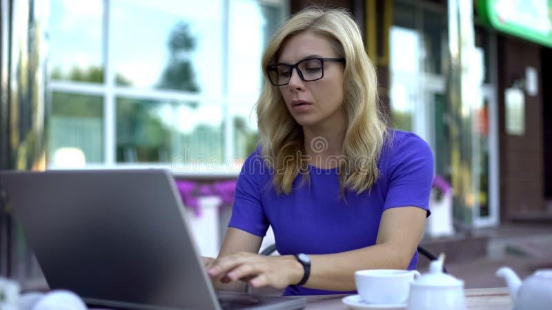 Pomyślny bizneswoman pracuje na laptopie, siedzi w kawiarnia tarasie, workaholic obraz royalty free