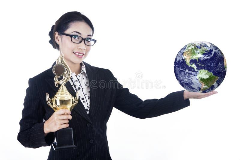 Pomyślny bizneswomanu chwyta trofeum i kula ziemska royalty ilustracja