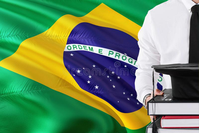Pomyślny Brazylijski studencki edukacji pojęcie Trzymający książki i skalowanie nakrętkę nad Brazylia zaznacza tło fotografia royalty free
