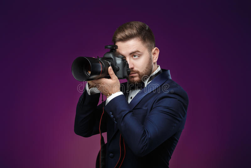 Pomyślny fachowy fotograf w smokingu use DSLR cyfrowej kamerze na ciemnym tle zdjęcie royalty free