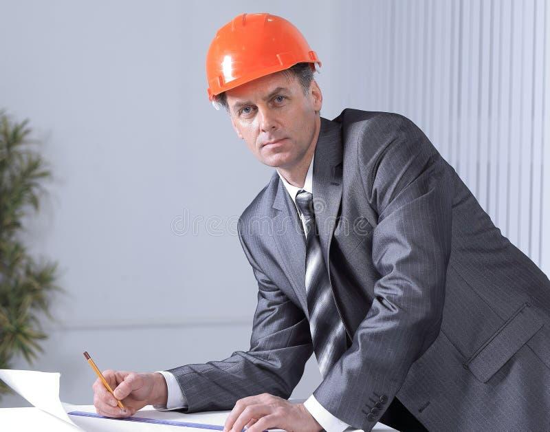 Pomyślny mężczyzna jest architektem pracuje przy biurem zdjęcie stock