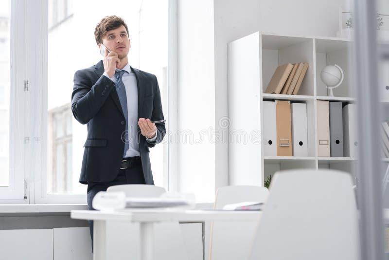 Pomyślny młodego człowieka mówienie telefonem w biurze fotografia royalty free