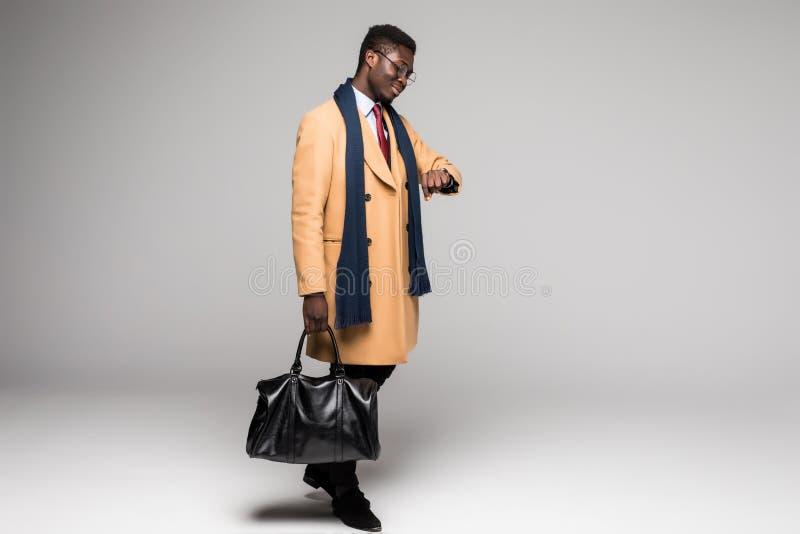 Pomyślny młody afro amerykański dyrektor wykonawczy w żakieta spojrzeniu przy zegarka czasem odizolowywającym na białym tle zdjęcia royalty free