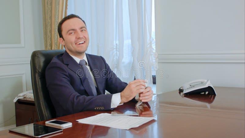 Pomyślny młody biznesmen liczy pieniądze, patrzeje szczęśliwy zdjęcie royalty free