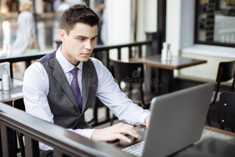Pomyślny młody biznesmen pisać na maszynie na laptopie w kawiarni zdjęcia stock