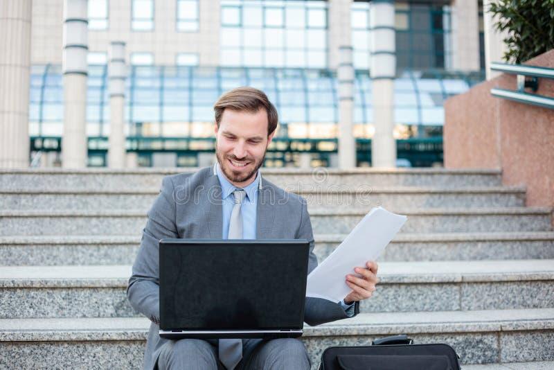Pomyślny młody biznesmen pracuje na laptopie przed budynkiem biurowym, sprawdza papierowych raporty zdjęcia stock