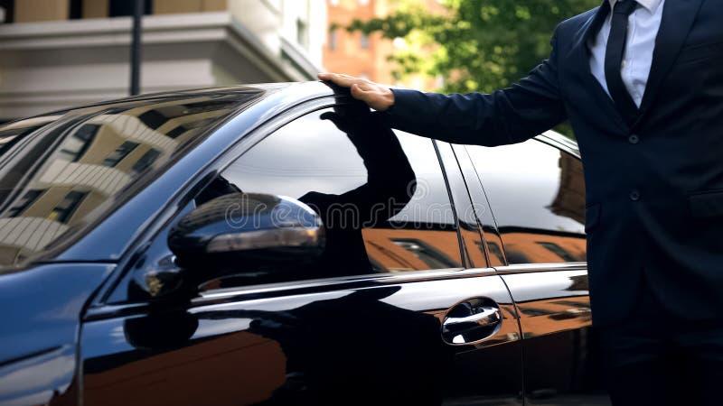 Pomyślny młody człowiek muska nowego kupującego biznesowego sedan, pomyślny rozpoczęcie fotografia stock