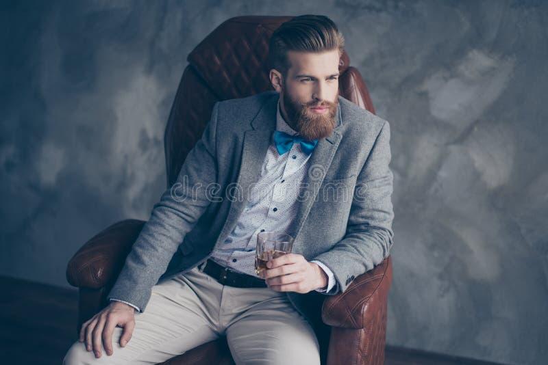 Pomyślny młody czerwony brodaty elegancki biznesmen w kostiumu z pe obrazy stock