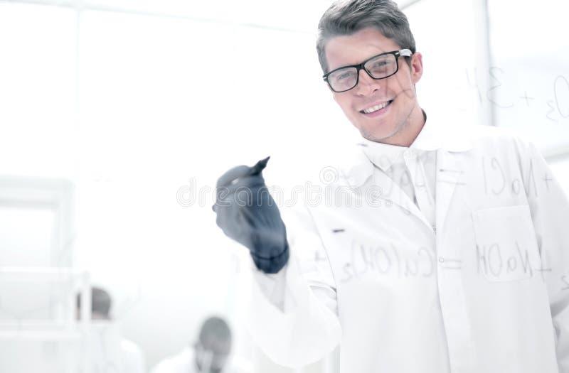 Pomyślny naukowiec pisze formule na szklanej desce zdjęcie royalty free
