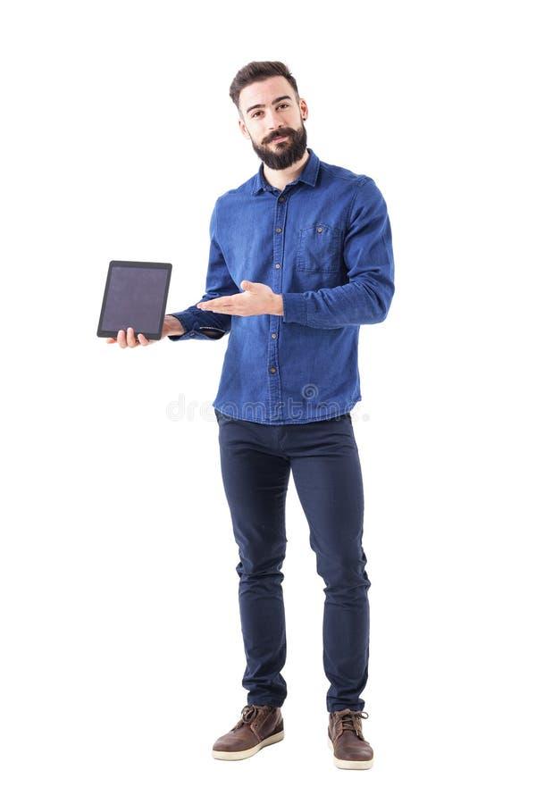 Pomyślny ono uśmiecha się ufny brodaty biznesowego mężczyzna mienie i przedstawiać pastylka patrzeje kamerę obrazy stock