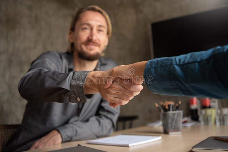 Pomyślny projektanta handshaking po wielkiej transakci w spotkaniu zdjęcia stock