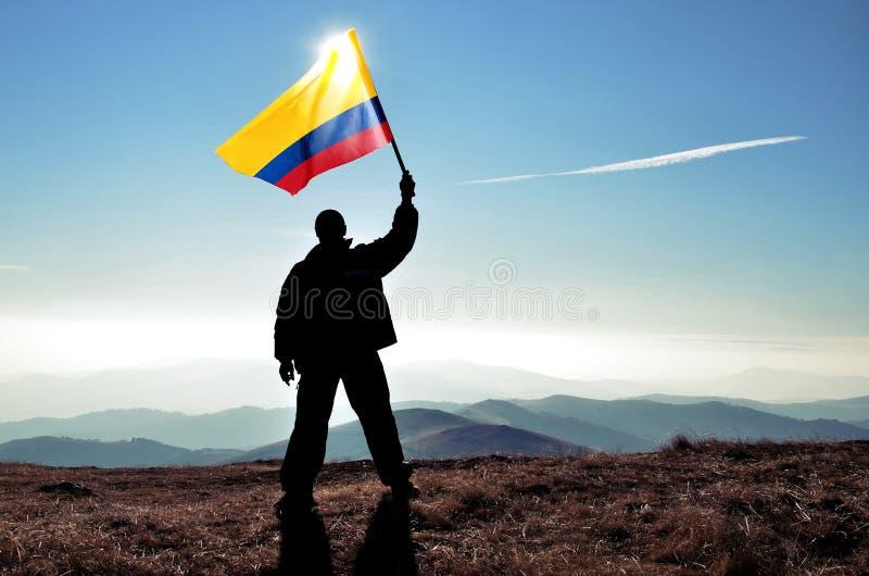 Pomyślny sylwetka mężczyzna zwycięzca macha Kolumbijską flaga na górze góry obrazy royalty free