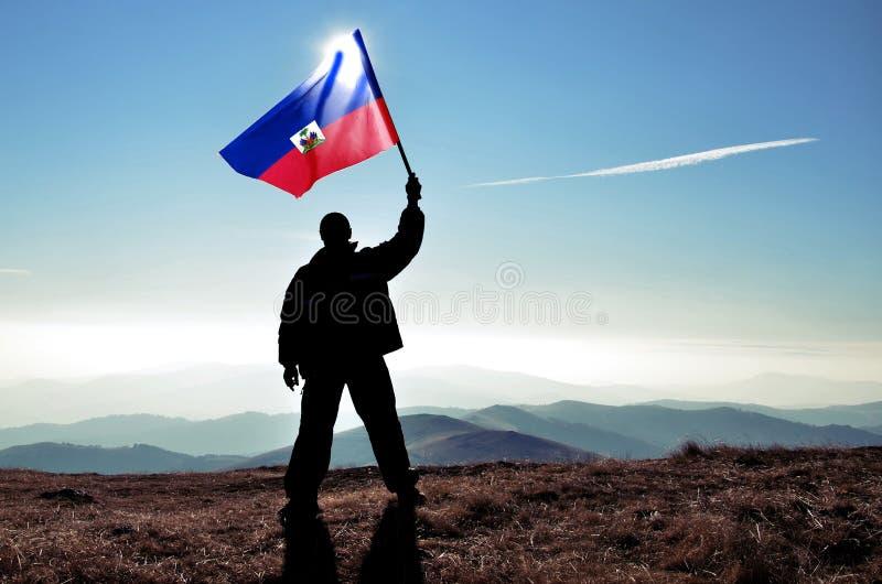 Pomyślny sylwetka mężczyzny zwycięzca macha Haiti flagę na górze góry zdjęcie stock