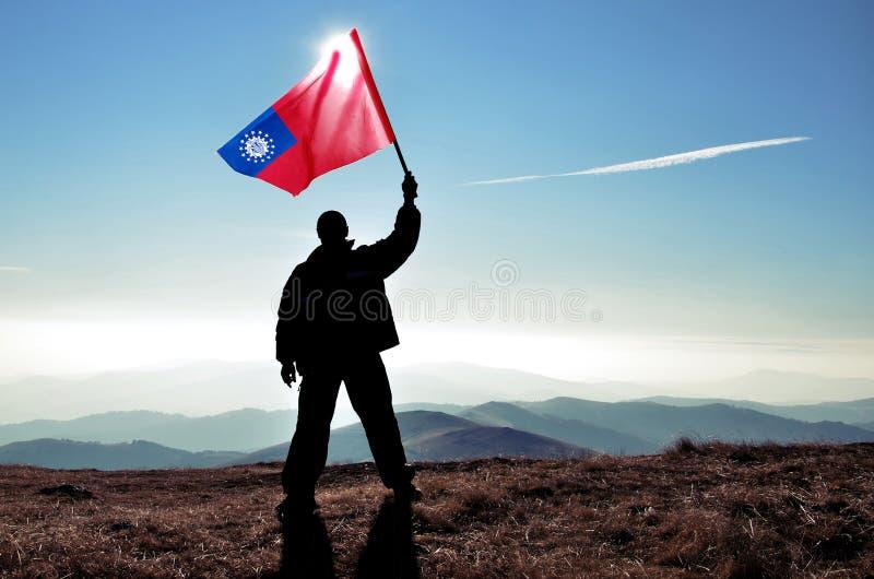 Pomyślny sylwetka mężczyzny zwycięzca macha Myanmar flagę na górze góry zdjęcie stock