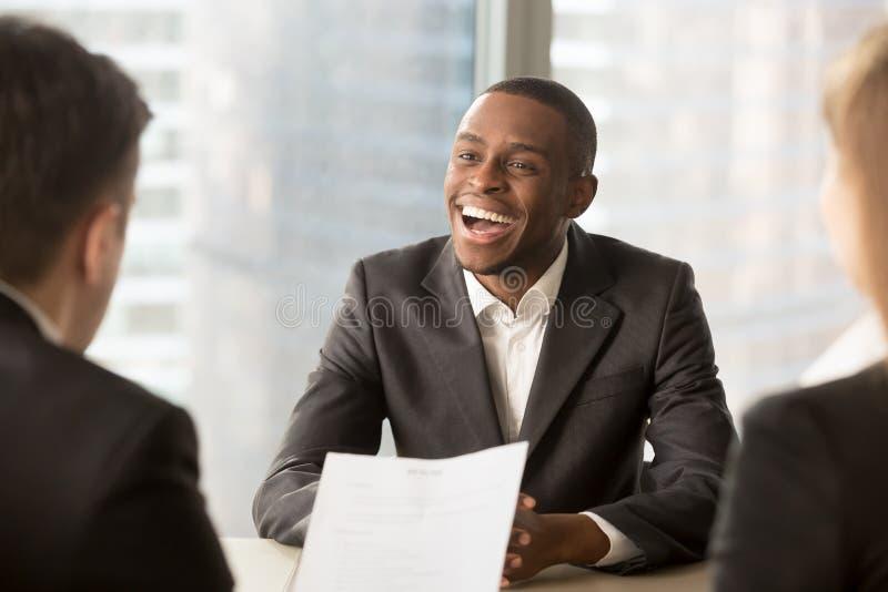 Pomyślny szczęśliwy czarny męski kandydat dostaje zatrudniający, dostawać pracę obrazy stock
