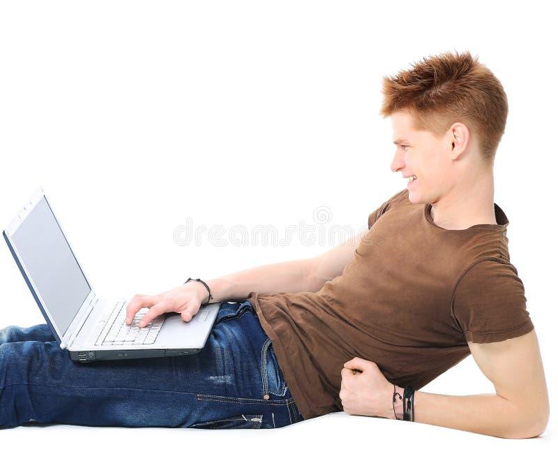 Pomyślny szczęśliwy mężczyzna lying on the beach na podłoga używać laptop i patrzejący monitoru zdjęcie stock