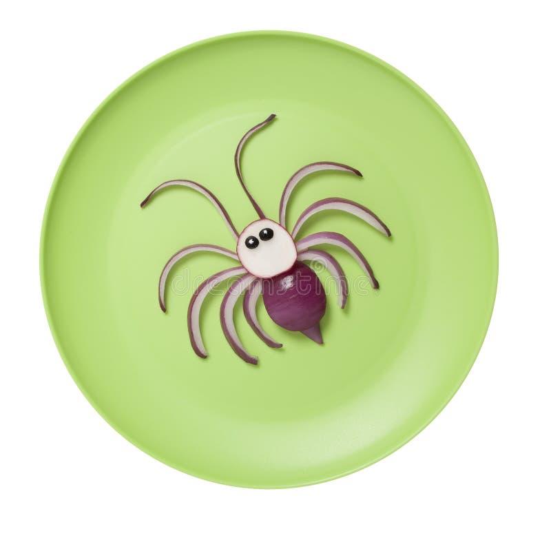 Pomysł robić pająka z cebulą na zieleń talerzu zdjęcia stock