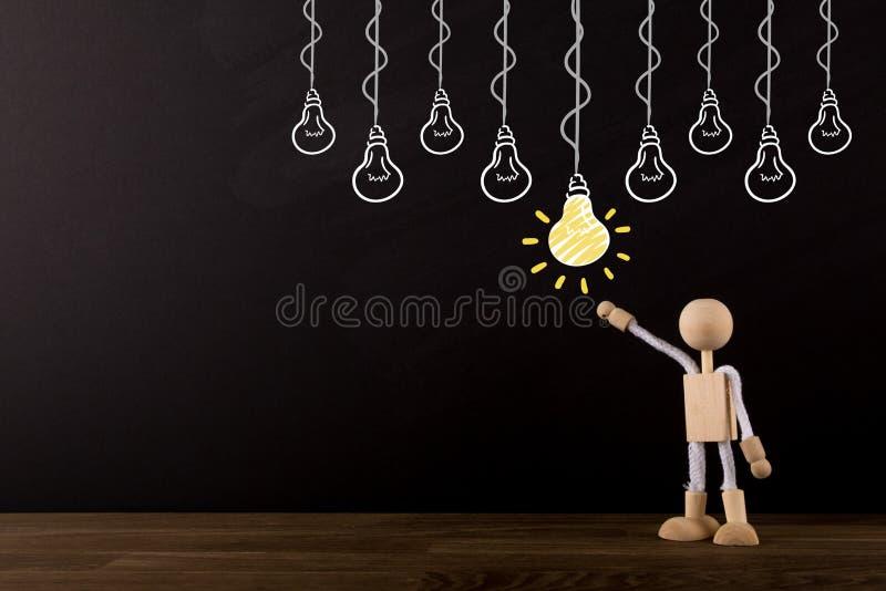 Pomysłu pojęcie, wybiera najlepszy pomysł, Brainstorming, Nowatorska Drewniana kij postać wskazuje przy żółtą żarówką fotografia royalty free