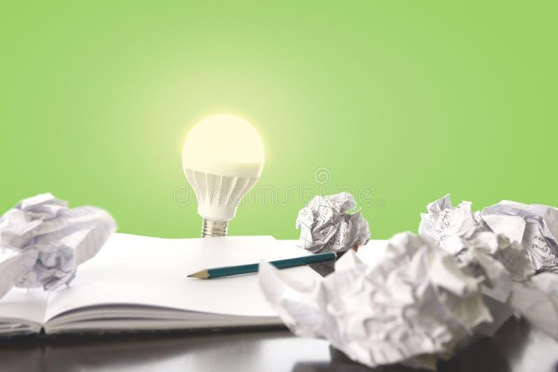 Pomysły próbni i błąd/pojęcia wizerunek z scrunched papieru, ołówka i żarówki oświetleniem w górę, fotografia stock