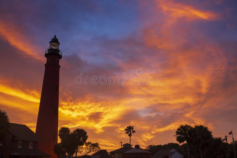 The Ponce de Leon Inlet Light glowing during sunrise. The Ponce de Leon Inlet Light, a lighthouse and museum located near Daytona Beach in central Florida, glows stock photo