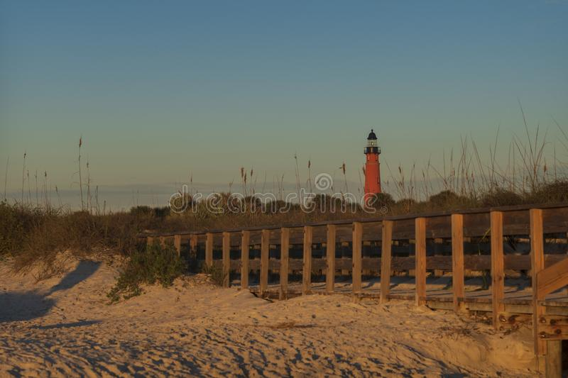 The Ponce de Leon Inlet Light glowing during sunrise. The Ponce de Leon Inlet Light, a lighthouse and museum located near Daytona Beach in central Florida, glows stock photos