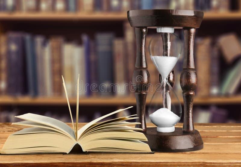 Poncez le fonctionnement dans le sablier et le livre ouvert dessus photos stock
