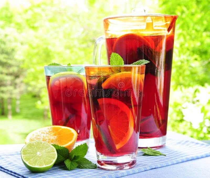 Ponche de fruta en jarra y vidrios imagen de archivo