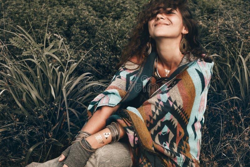 Poncio d'uso della bella donna di boho sul campo verde fotografia stock libera da diritti