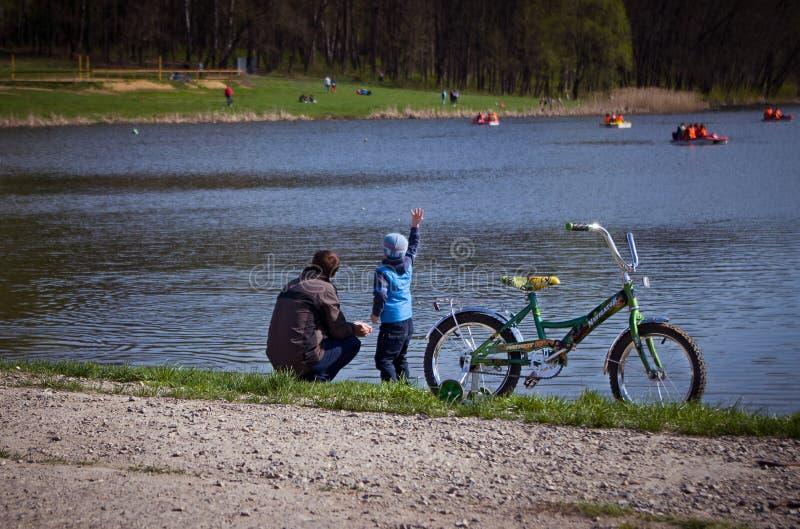 Pond в парке, камнях ходов мальчика в воду стоковые изображения
