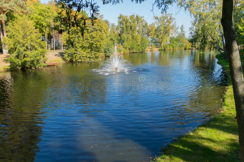 Pond with clear water and a small fountain against the background of green lawns. For your design stock image